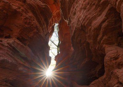 Die Sonne spitzelt durch ein Felsspalt am Altschlossfelsen