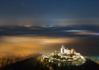Das Hambacher Schloss über der vom Nebel bedeckten Rheinebene bei Nacht